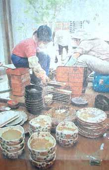 民宿の食堂で泥でつかった食器をひとつひとつ消毒し洗浄する人たち=7月24日、福井市・安波賀にて