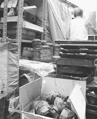 泥に漬かった漆器を前に「夫婦だけでは、片付けられない」という卸業の男性(76)=15日、福井県鯖江市