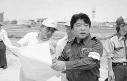 足羽川堤防の決壊地を視察する仁比聡平参院議員(中央)=7月4日、福井市にて