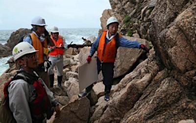 もんじゅの現地調査で、海岸に断層が発達しているか調べる原子力規制委員会の専門家ら=7月18日午前、福井県敦賀市(代表撮影)