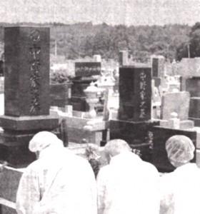 防護服姿で先祖の墓に手を合わせる住民。奥には原発が見えます=8月15日午前、福島県大熊町