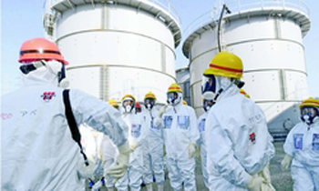 (写真)汚染水貯蔵タンク群を見上げる志位和夫委員長(中央)ら日本共産党の視察団=3月9日、東京電力福島第1原子力発電所