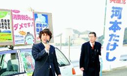美浜原発を背に街頭から訴える河本たけし候補(左)=2月16日、福井県美浜町