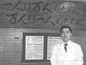 病院の入り口に掲げられた「一人は万人のために 万人は一人のために」の前に立つ国井綾(りょう)医師