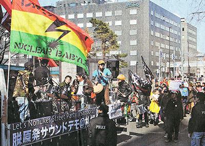 北海道電力本店そばで「原発いらない」と行進する人たち=4月20日、札幌市