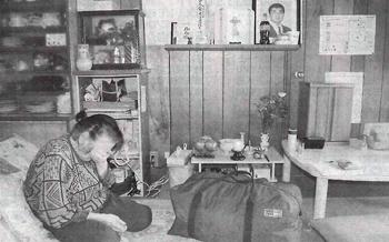 居間に置かれた骨つぼ、遺影の前で悲しみをこらえきれない堅さんの母、チエさん。手前は遺品のかばん=新潟県五泉市