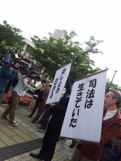 勝訴判決を受けて、垂れ幕を掲げる寺田弁護士(左)