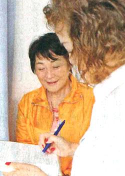呼びかけに応じ署名する市民(手前)=5月17日、鹿児島県いちき串木野市