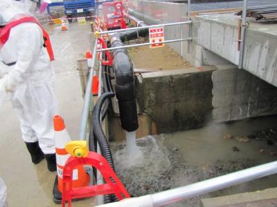 一時貯留タンクから海につながる水路に流れる地下水=5月21日午前、福島第1原発(東電提供)