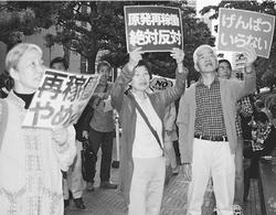 (写真)「再稼働するな」「いますぐ廃炉」と関電本店前で訴える人たち=5月23日、大阪市