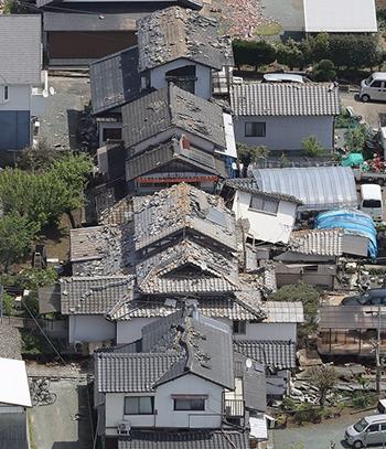 地震の影響で瓦が落下した家屋=4月15日午前、熊本県益城町(時事通信ヘリより)