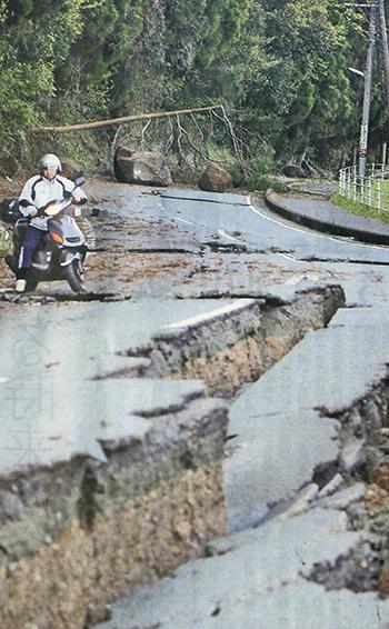 地震の影響で段差ができた道路=4月16日午前、熊本県西原町