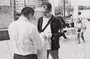 署名にこたえる男性=10月11日、東京・新宿駅前