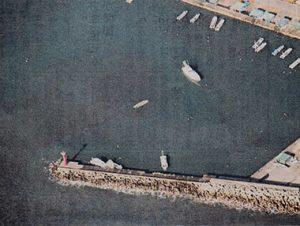 福島県沖の地震に伴う津波で転覆したとみられる小型ボート(中央)=11月22日、宮城県七ヶ浜町の漁港(海上保安庁提供)